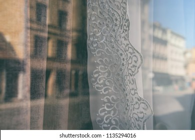 Reflection of the city in a window with curtains