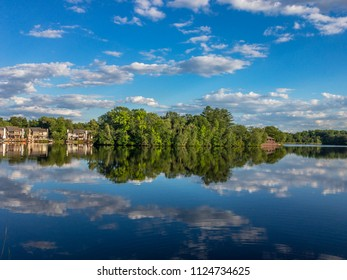 Reflection of the cloudy sky in the calm water of little lake