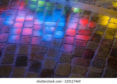 reflection of colored light onto the pavement at night
