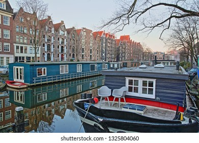 Reflection of colorful heritage buildings and houseboats along Brouwersgracht Canal in Amsterdam, Netherlands. Picture taken before sunrise.