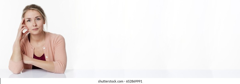 reflection concept - concerned beautiful young blond woman sitting at a sparse desk for patience and thought, white copy space, long banner