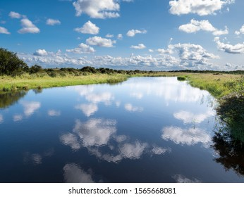 Reflection of cumulus clouds in water of canal in marshland on West Frisian island Schiermonnikoog, Netherlands