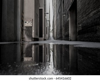 Reflection of a dark city alley way in a rain puddle