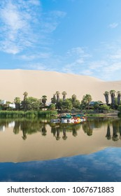Reflection of the dunes on the water of the Huacachina lagoon in Peru