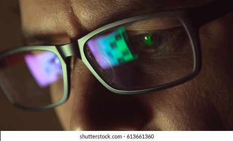 Reflection at eyeglasses of man: looking at a website