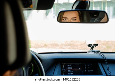 Reflection of female eyes in rearview mirror of a car