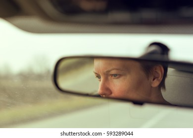Reflection of female face in car rearview mirror while overtaking someone on open road, retro toned