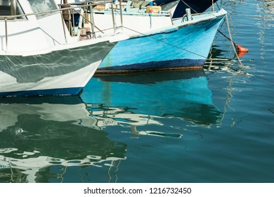 Reflection of fishing boats in the sea water