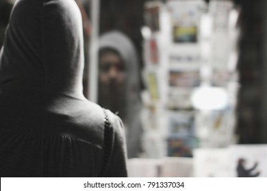 Reflection of a girl face in a shop window at night . Concept of a depression,  sorrow, mental illness, solitude, jobless, anxiety.