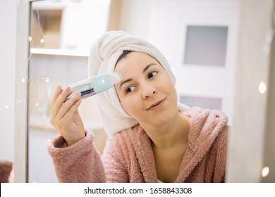 Reflection of a girl using ultrasonic skin scrubber