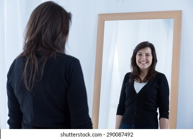 Reflection of girl wearing a fake smile
