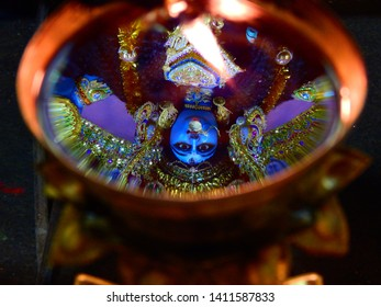 Reflection of Goddess Kali on a oil lamp during Kali Puja at Kolkata ,West Bengal , India.