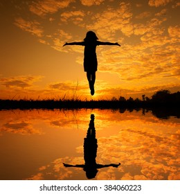 Reflection of  Reflection of Happy woman jumping and sunset silhouette,water reflect