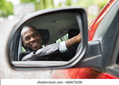 Reflection Of Happy Young Businessman In Rear View Mirror Of Car