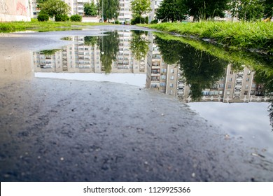 Reflection of houses in a puddle on asphalt, summer landscape