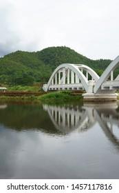 reflection image of The Tha Chomphu Railway Bridge or White Bridge, railway bridge in Mae Tha District, Lamphun, history landmark of Thailand