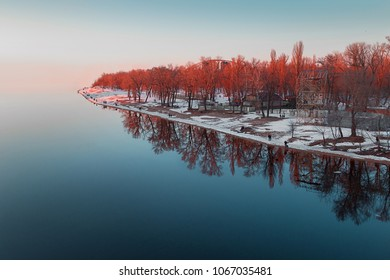 Reflection of the island in the water. Red trees reflected in the water.