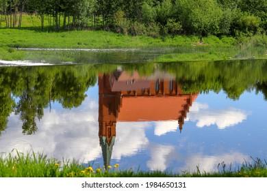 Reflection of the kirche of Krasnoznamensk in the river water of Sesupe, Kaliningrad region - Shutterstock ID 1984650131