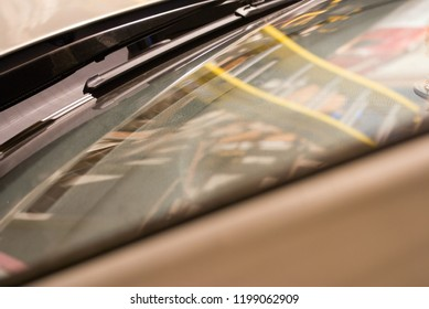 Reflection of a ladder and otherwise messy garage in the windshield of a car