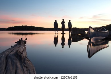 Reflection in a lake of people looking at sunset.