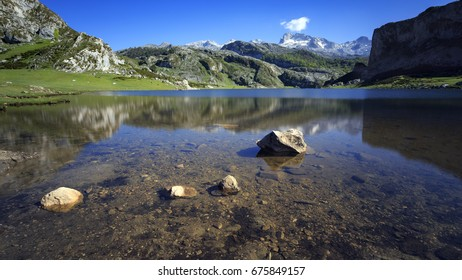 Reflection in a lake with rocks and mountains in the background.