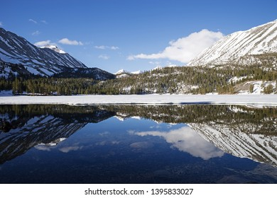 reflection of Little Lakes Valley in Rock Creek Lake on a spring morning with a lot of snow
