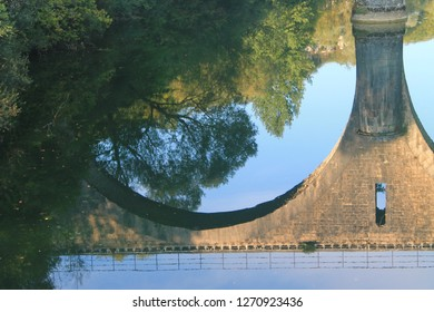 Reflection in the Loue river of the bridge near the Cleron Castle in Franche-Comté, France