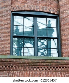 Reflection of Manhattan Bridge Captured in a Brick Building Window in Dumbo, Brooklyn, New York.