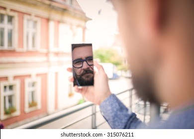 Reflection of a man's face in mobile phone