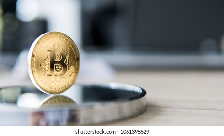 Reflection in the mirror of Bitcoin coin with a laptop on background. Cryptocurrency investment Digital currency. Virtual money. Metal coins of bitcoin. Bussiness, commercial.