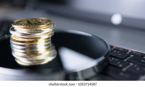 Reflection in the mirror of Bitcoin coin on a top of other crypto coins on keyboard of laptop. Cryptocurrency investment Digital currency. Virtual money. Metal coins of bitcoin. Bussiness, commercial.