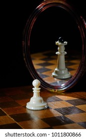 the reflection in the mirror of a chess Queen and pawn