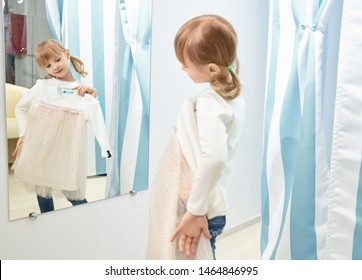 Reflection in mirror of cute girl. Little girl choosing and trying pink and white dress in fitting room with blue curtains. Child looking at mirror in mall or clothing store.
