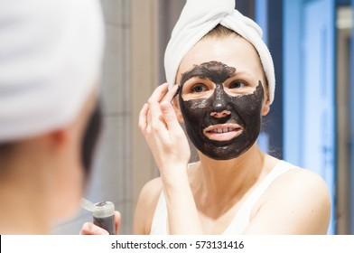 The reflection in the mirror a young attractive girl, which requires cosmetic mask on her face, in the bathroom