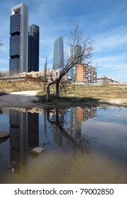 Reflection of modern towers puddle in wasteland