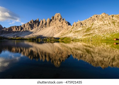 Reflection of Monte Paterno Mountain on a lake in Dolomites Italy. Tre Cime Lavaredo. Reflection. Blue Sky. Sunny. Hiking.
