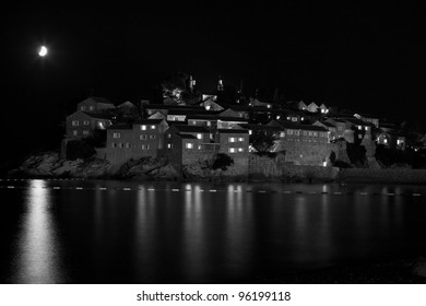 reflection of moon and  lights in water Adriatic Sea on background walls, old houses Sveti Stefan