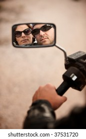 Reflection of Motorcycle Driver and Rider in Rearview Mirror