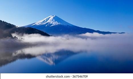 Reflection of Mount Fuji in calm water and morning fog.   Vacation place with mount Fuji on background. Kawaguchiko lake in Fujikawaguchiko, Yamanashi Prefecture, Japan.