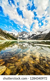 Reflection of a mountain in Lake of the Hanging Glacier, in the Purcell Mountain Range, British Columbia, Canada