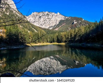 Reflection of the mountain landscape in a calm surface of Green Lake, Austria. The reflection is in the shade. High mountains are surrounded by dense forest. Spring in Alpine valley. Mirroring effect