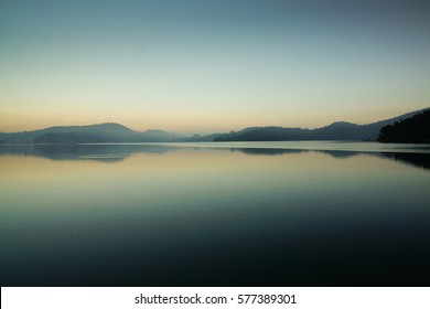 Reflection of mountain range in clear and still water at the Famous Sun Moon lake in Taipei depicting peaceful morning. This Beautiful landscape with Sunrise at dawn is a popular tourist attraction.