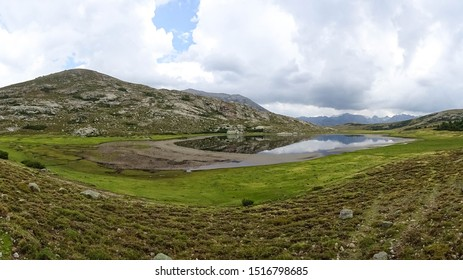 reflection of mountain range on water surface of Nino Lake (Lac de Nino) located on popular hiking trail GR20 leading through Corsica, french island in Mediterranean Sea, France, Europe