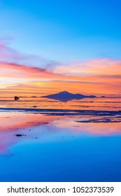 Reflection of the mountain, sunset and car in the Salar de Uyuni, Bolivia. One of the best sunset scene in the world.