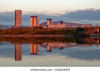 Reflection of mountains and industrial buildings in the lake at sunset. September 8, 2018, Norilsk Talnakh