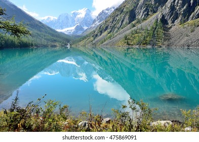 The reflection of the mountains Skazka and Krasavitsa (Tale and Beautiful) in a Large Shavlinskoye lake, Altai mountains, Russia