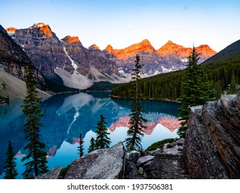 reflection of mountains in a turquoise lake early in the morning with red on the peak