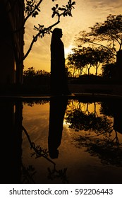 reflection of a muslim woman in burqa standing near a water body at dusk
