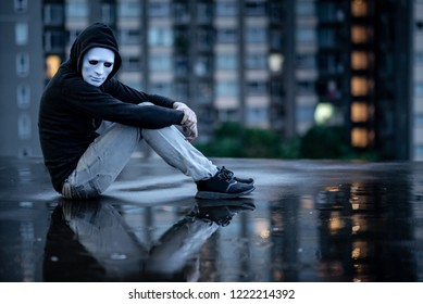 Reflection of mystery hoodie man in white mask hugging his knees sitting in the rain on rooftop of abandoned building. Bipolar disorder or Major depressive disorder. Depression concept