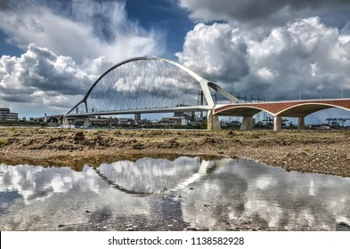 Reflection of new city bridge De Oversteek (The Crossing) in a puddle in the floodplain of the river Waal near Nijmegen, the Netherlands